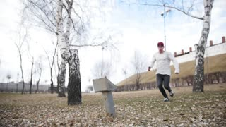 Slow motion - acrobatic parkour teenager doing somersault