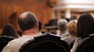 Spectators are watching theatrical performance - bald man and woman