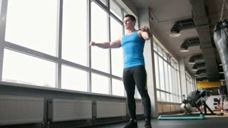 Sport in the gym - young strong man doing exercises for warm-up