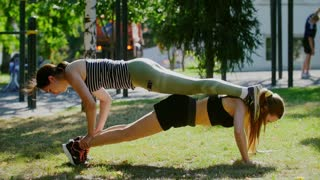 Sporty girl performs pushups with weight in the park, her friend lies on top as weight