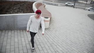 Street acrobatics - teenager jumps a flip at park, parkour, slow motion