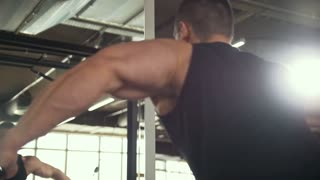 Strong man bodybuilder workout in front of a mirror in a gym