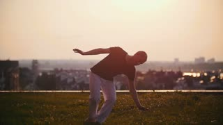 Strong man makes somersaults from the martial art of capoeira on the background of a beautiful summer sunset