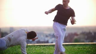 Strong men demonstrate the skills of Brazilian martial art of capoeira on the grass against the beautiful summer sunset