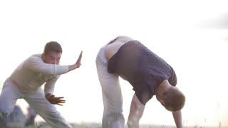 Strong men perform tricks with their feet, dancing Brazilian capoeira on the grass