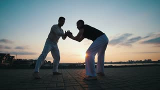 Strong men train, dance capoeira on the asphalt over the city, against the beautiful sky