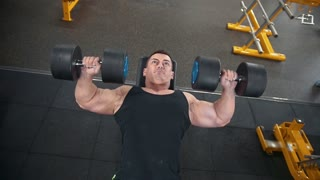 Strong muscular man does dumbbells exercises in a workout room