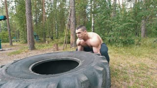Strong muscular man lifting a huge rubber wheel, workout in the forest