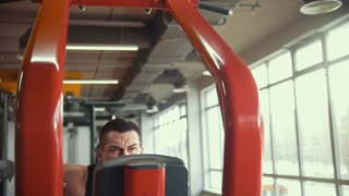 Strong young man doing exercise program in workout room