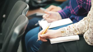 Students participating in a lecture and taking notes - people writing into their notebooks
