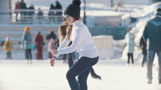 Teen girl skating on outdoor public ice rink