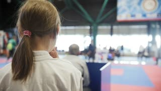 Teenager karate sports girl watching fight on tatami - spectator - Karate competition - slow-motion