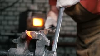 The blacksmith sets in the vise a red-hot metal