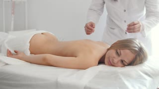 The doctor sticks needles into the woman's body on the acupuncture
