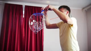 The man made a spectacular performance with soap bubbles. In one large bubble blew lots of little bubbles.
