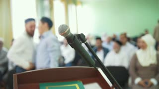 The microphone on the desk in front of crowd of muslim people on mass rally