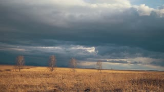 The movement of clouds in the spring field in cloudy weather, blurred