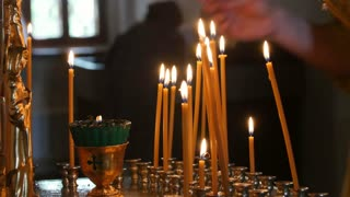 The parishioner put a candle inside an Orthodox church