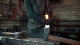 The smith gives shape with a hammer to a red-hot metal object, slow-motion