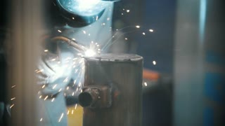 The welder welds metal parts at the plant, industrial welding