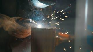 The welder welds metal parts