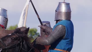 There is a battle of men in historical armor at the tournament, at the festival of the middle ages