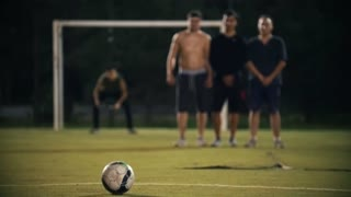 Three men built a wall of penalty, at the gate is the goalkeeper, the ball flies and hits the gate, night shooting