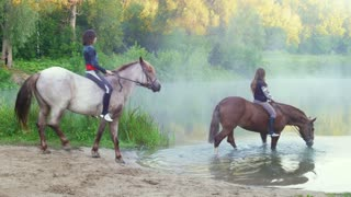 Two beautiful young woman with their horses swimming in the lake at dawn