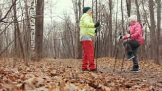 Two elderly woman in autumn park have training - nordic walking