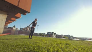 Two female cheerleaders workout outdoors at sunny day