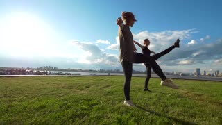 Two female gymnast workout outdoors at cityscape