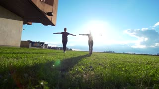 Two female gymnast workout simultaneously at summer sunset