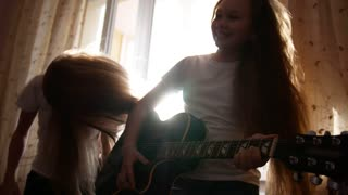 Two female teens have unny and playing hard rock music with instruments in front the window at home