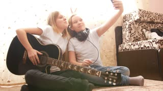Two female teens making selfie and posing with musical instruments sitting on the floor at home