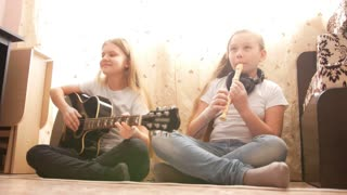 Two female teens playing musical instruments at home