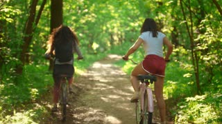 Two girls walk on their bikes in the Park, the girl sits on the bike