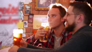 Two guys sit at the bar, drinking beer and talking