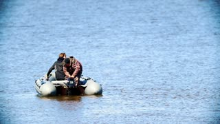 Two men spending leisure time on the lake in an inflatable boat