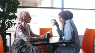 Two muslim women drink coffee and communicate