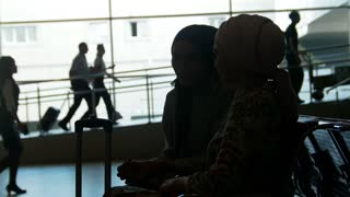 Two muslim women talk to each other in the waitroom at airport