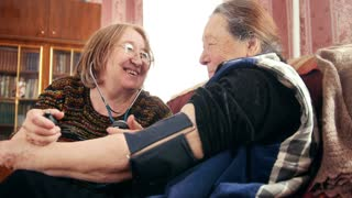 Two pensioners - senior ladies have fun - checking health state with manometer - measures pressure, pensioners healthcare