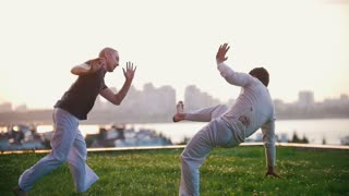 Two strong men show elements from the Brazilian martial art of capoeira on the grass