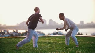 Two strong men show elements of capoeira wrestling on the grass in summer