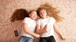 Two teen girls lying on the floor, their hair spread over the floor