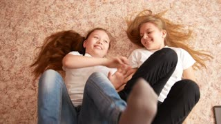 Two teenagers sisters girls lying on the floor - playing and have fun