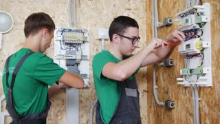 Two teenagers working with electric equipment in workshop