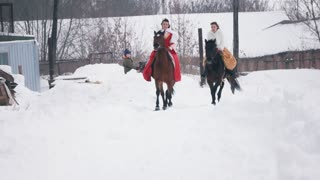 Two young brunettes in a dresses galloping fast on a horse through the snow-covered field in the winter