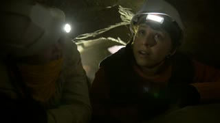 Two young female hikers talking and looking around in the dark cave
