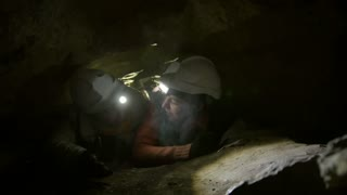 Two young hikers explorers stuck in the narrow hole in dark cave