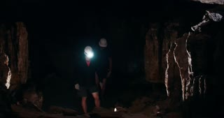 Two young men speleologists with flashlight walks in a dark cave